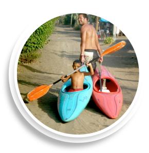 man dragging boy in canoe along dirt road